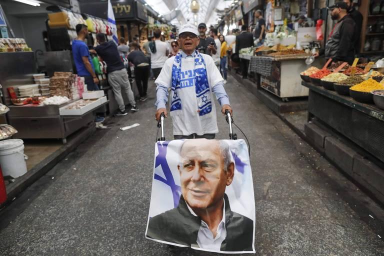 Homem empurra carrinho com pôster do premiê Binyamin Netanyahu em mercado em Jerusalém