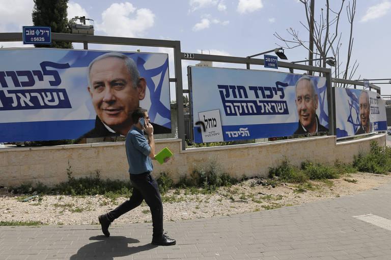Homem passa por pôster de campanha do atual primeiro-ministro de Israel, Binyamin Netanyahu, em Jerusalém