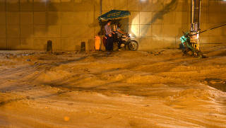 People are seen on a street filled with mud during heavy rains in the Jardim Botanico neighborhood in Rio de Janeiro
