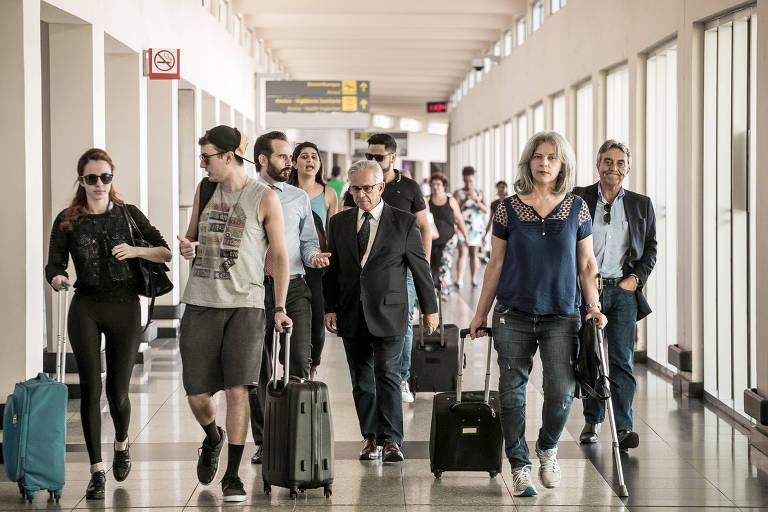 Pessoas em corredor com malas de carrinho