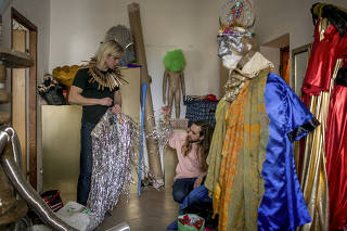 Maciej Gosniowski, left, who works as one of only a handful of drag performers in the country, prepares costumes for a performance in Warsaw, Poland.