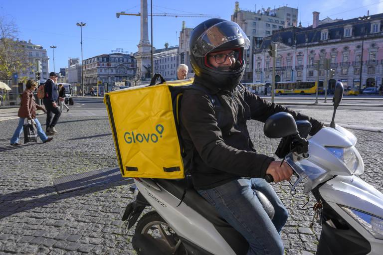 """Homem de capacete montado em motocicleta carrega mochila amarela onde se lê """"glovo"""""""
