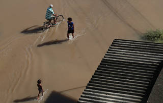 Residents are pictured at a flooded street during heavy rains in the Guaratiba neighborhood in Rio de Janeiro