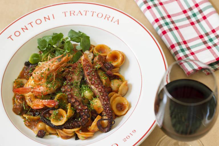 prato de massa com frutos do mar ao lado de uma taça de vinho tinto e um guardanapo de tecido xadrez