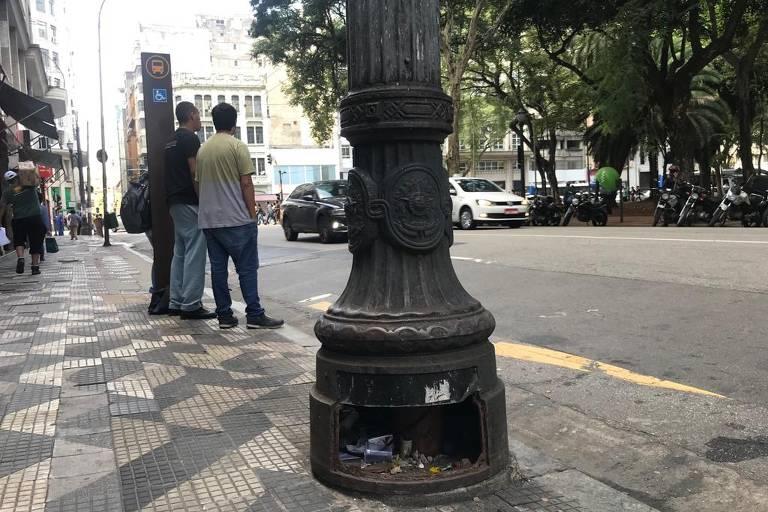 Poste na Praça da República, no centro de SP, que teve a tampa furtada e tem acúmulo de lixo
