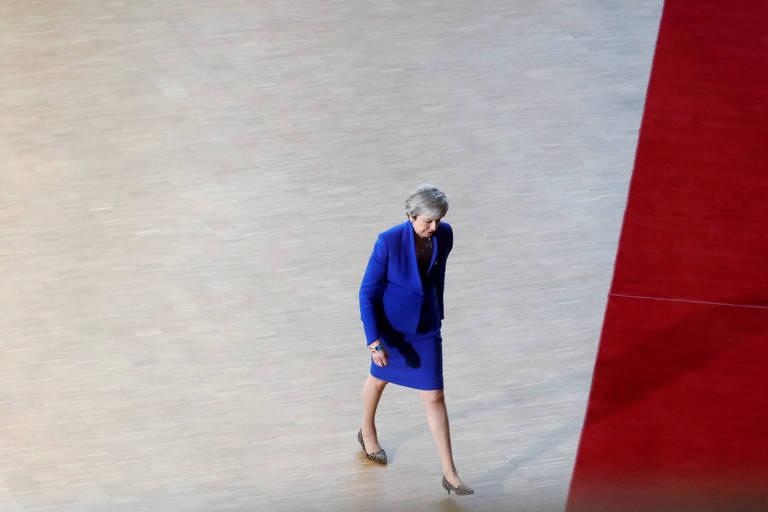 A primeira-ministra britânica, Theresa May, veste terno azul royal e anda por um tapete vermelho