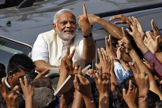 File photo of Hindu nationalist Modi showing his ink-marked finger to his supporters after casting his vote in Ahmedabad