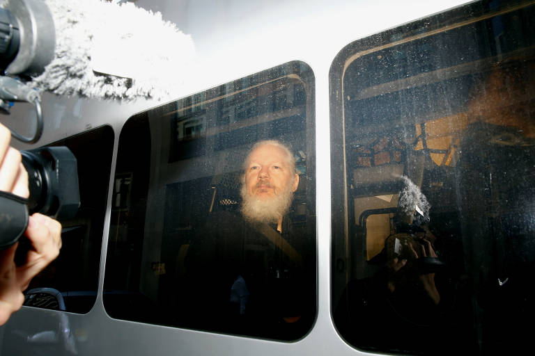Assange foi levado pela polícia em uma van  Henry Nicholls
