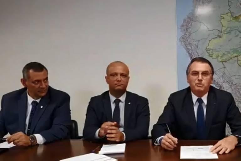 O presidente Jair Bolsonaro (PSL) em sua live semanal, ao lado do porta-voz, general Rêgo Barros, e do deputado Major Vitor Hugo (PSL-GO)