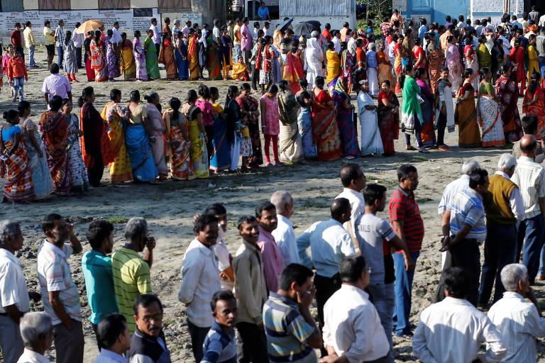 Eleitores indianos fazem fila para votar durante a primeira fase das eleições gerais no distrito de Alipurduar, na Bengala Ocidental, Índia