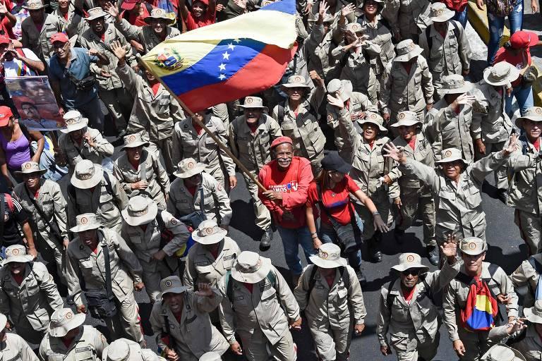 Homem carrega bandeira venezuelana em meio a membros de milícias durante protesto convocado pelo ditador Nicolás Maduro