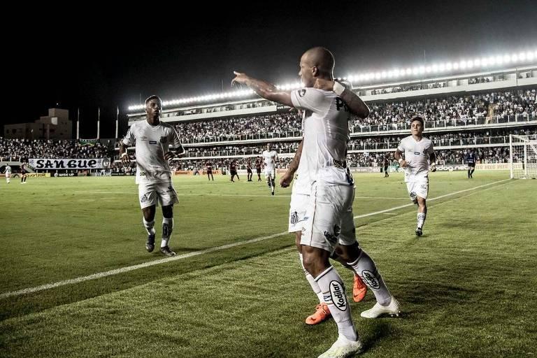 Fora do campo, de costas para a imagem, o meio-campista uruguaio Carlos Sánchez celebra seu primeiro gol no duelo com o Atlético abraçado a Jean Mota e esperando as chegadas de Rodrygo e Soteldo