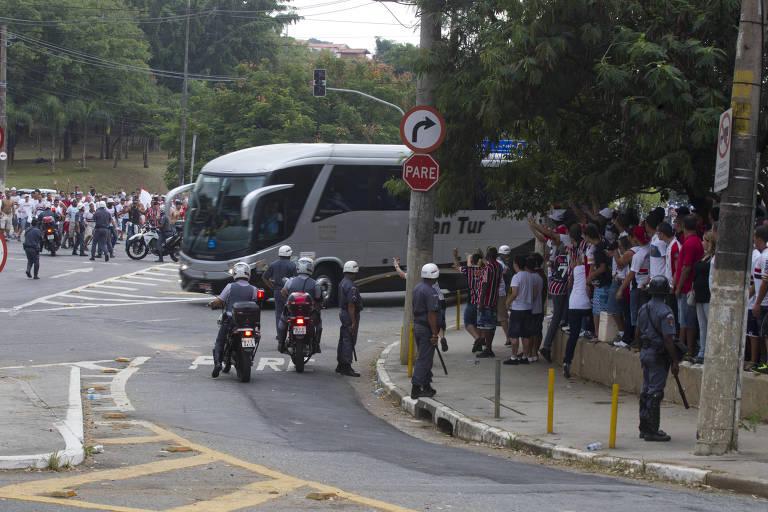 Torcedores do São Paulo cercam o ônibus do Corinthians, na chegada ao Morumbi, para hostilizar a delegação alvinegra nas semifinais do Campeonato Paulista de 2013; Timão ameaça não jogar se o veículo for apedrejado