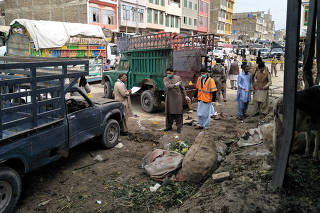 Members of the bomb disposal unit survey the site after a blast at vegetable market in Quetta,