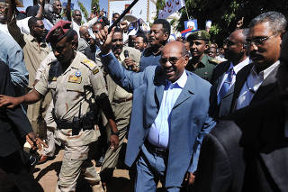 FILE-- President Omar Hassan al-Bashir of Sudan, waves with his baton as he enters a rally where he addressed thousands of supporters in downtown Khartoum, Sudan, on March 5, 2009.