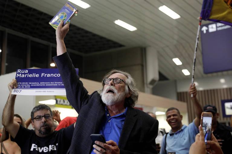 """""""Autoproclamado"""" presidente, o ator José de Abreu toma """"posse"""" no aeroporto do Galeão, no Rio, e é recepcionado por dezenas de pessoas. Abreu levanta uma constituição federal com a mão direita. Atrás, manifestantes riem, aplaudem. Um deles está erguendo uma placa com o nome da ex-vereadora Marielle Franco."""