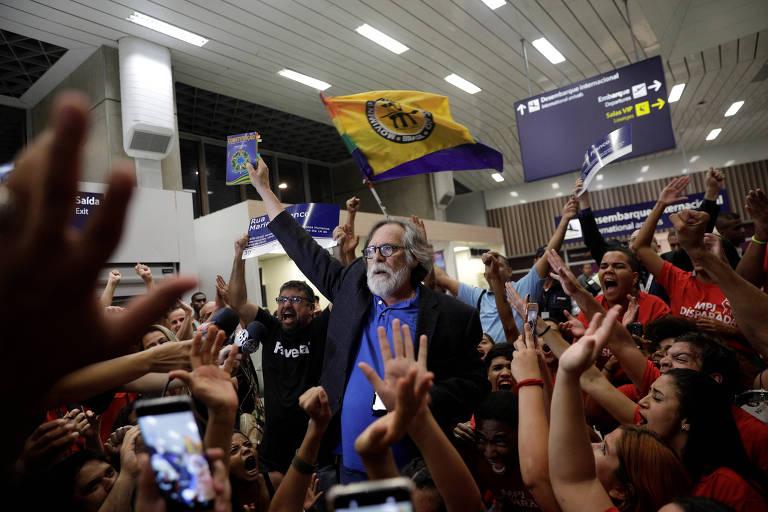 """""""Autoproclamado"""" presidente, o ator José de Abreu toma """"posse"""" no aeroporto do Galeão, no Rio, e é recepcionado por dezenas de pessoas. Ele levante uma constituição com a mão direita. Atrás, militantes gritam e festejam."""