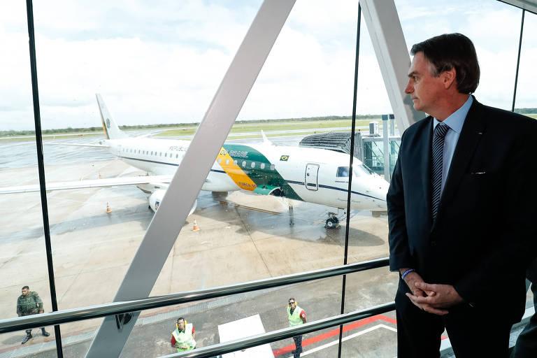 Presidente olha pelo vidro de aeroporto, com avião ao fundo
