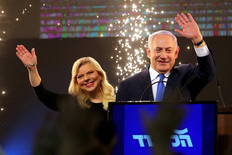 O primeiro-ministro de Israel, Biyamin Netanyahu, ao lado de sua mulher, Sara, acena para apoiadores em Tel Aviv