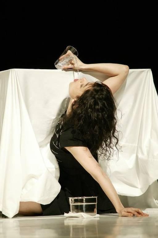 A bailarina, com o corpo parcialmente embaixo de uma mesa, que é forrada por toalha branca, bebê um copo d'água.