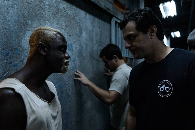 O carcereiro Adriano (Rodrigo Lombardi) revista o preso Califa (Sergio Menezes ) na segunda temporada de 'Carcereiros'