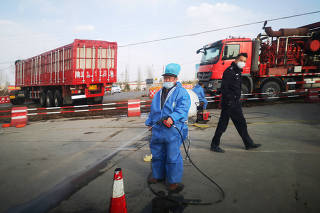 Worker disinfects a vehicle as a police officer walks by, near a farm where African swine fever was detected, in Yulin