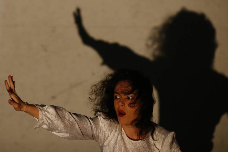 """A bailarina Morena Nascimento faz coreografia durante ensaio de seu novo espetáculo """"Rêverie"""". A imagem mostra a projeção de sua sombra na parede ao fundo, dando intensidade à coreografia."""