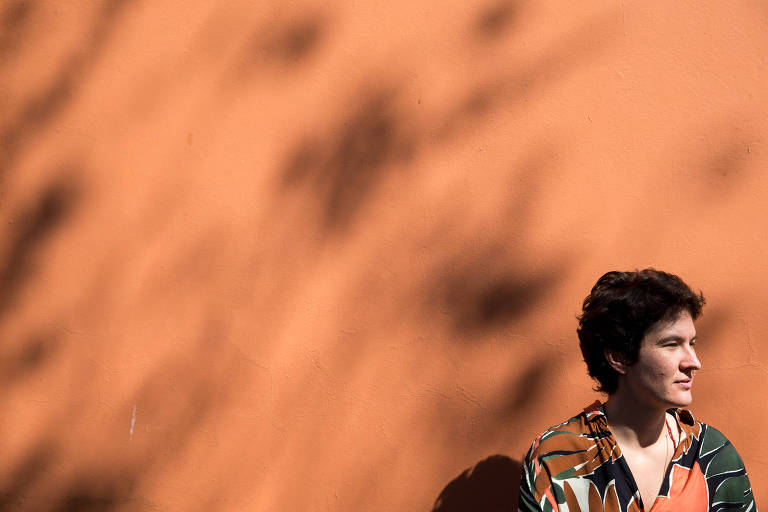 A escritora posa para a foto; ela usa camisa estampada e, ao fundo, há uma parede toda laranja.
