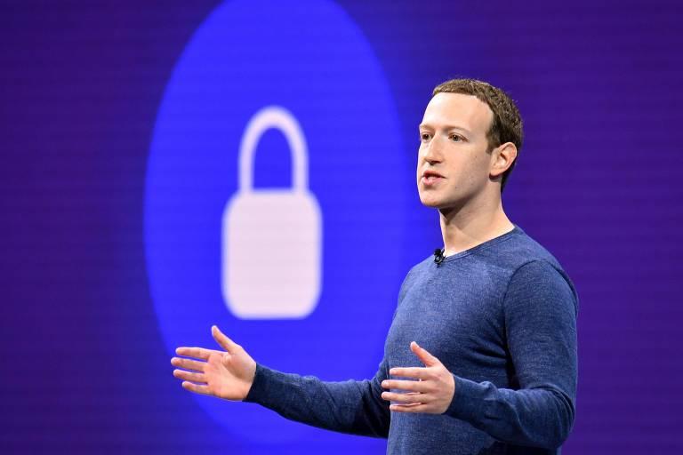 Mark Zuckerberg discursa em evento com fundo azul e cadeado branco.
