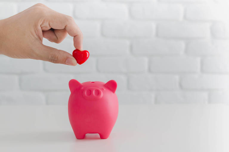 Mão coloca coração vermelho dentro de porquinho cor de rosa
