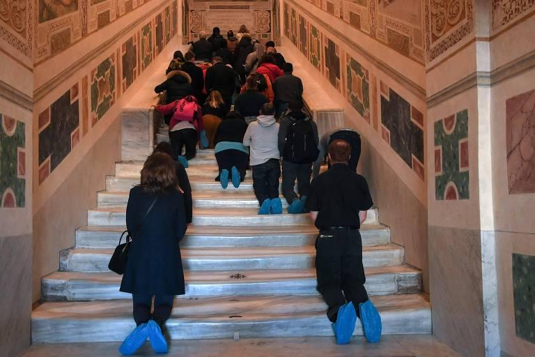 Fiéis se ajoelham nos degraus da recém-restaurada Scala Santa (Escada Santa) em Roma