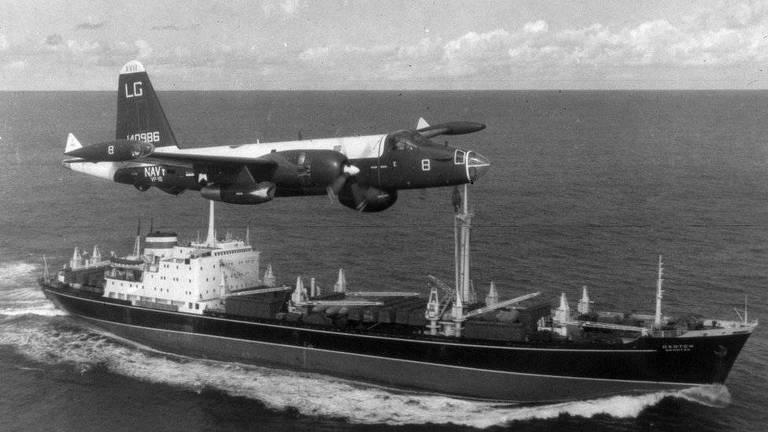 foto antiga em preto e branco mostra avião pequeno sobrevoando grande barco em alto-mar