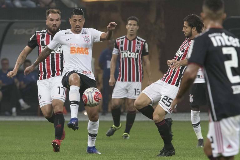 Cercado por jogadores do São Paulo, o volante corintiano Ralf tenta chutar a bola durante Majetsoso da fase de grupos