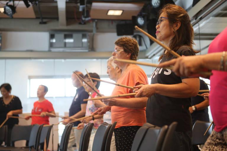Senhoras em círculo fazem exercícios com baquetas em sala de aula