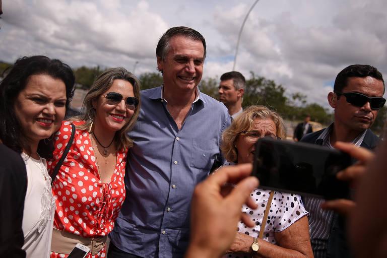 O presidente Jair Bolsonaro tira fotos com apoiadores ao sair do Palácio da Alvorada