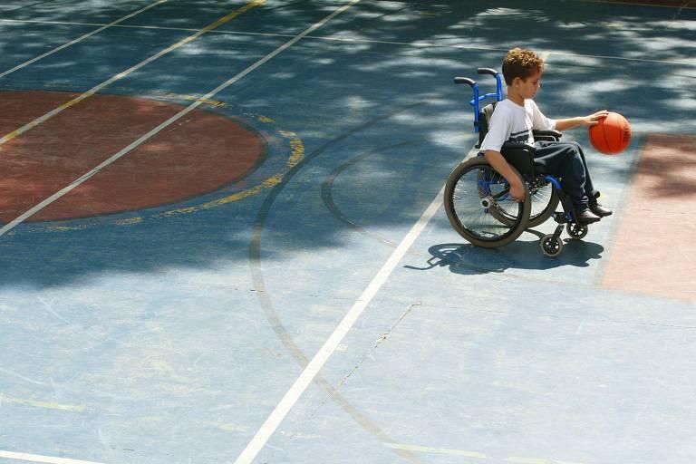 Menino em cadeira de rodas está em uma quadra de basquete brincando com uma bola