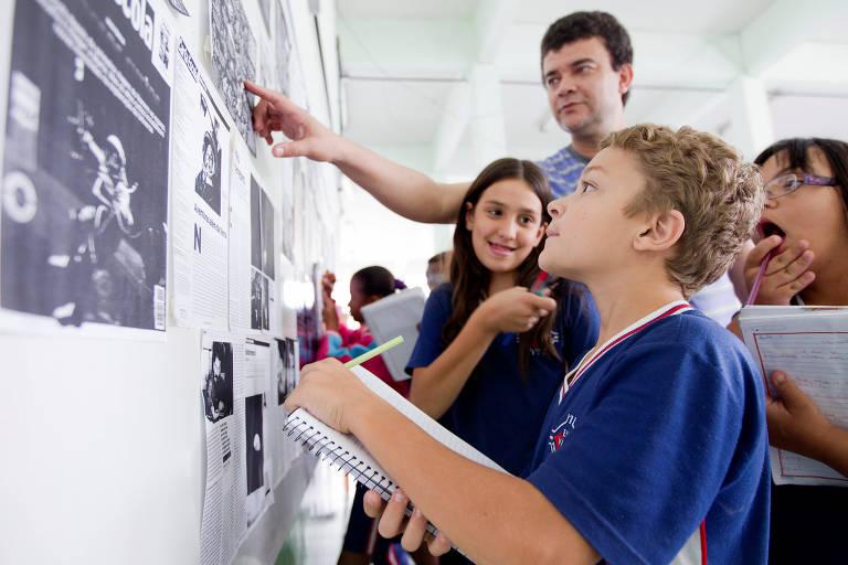 Garoto loiro olha para o quadro de atividades da sala de aula com um caderno nas mãos. Ele está cercado por colegas e pelo professor, que aponta para algo no quadro