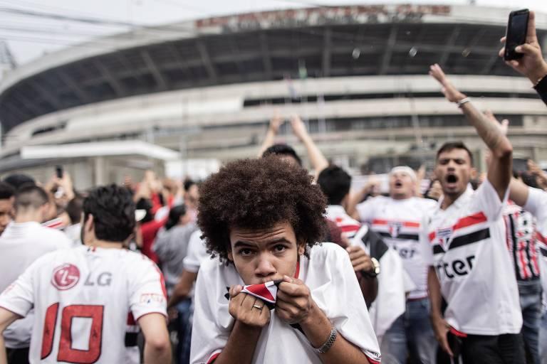 Torcedor do São Paulo beija o escudo do time na camisa. Atrás dele estão outros vários torcedores do clube