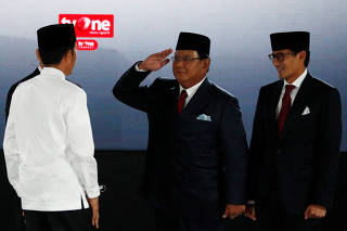 Indonesia's President Joko Widodo is greeted by presidential candidate Prabowo Subianto and his running mate Sandiaga Uno before a debate in Jakarta