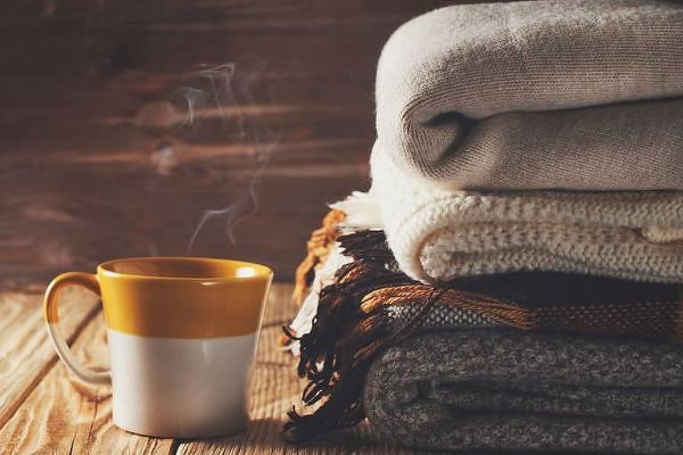 Xícara de chá ao lado de mantas dobradas