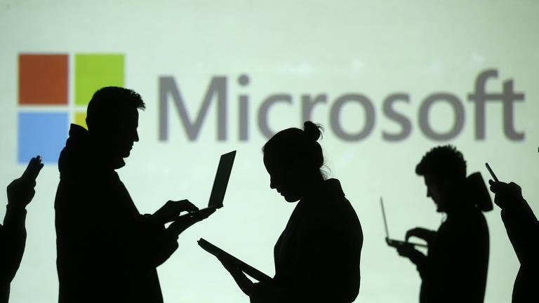 Silhuetas de cinco pessoas usando tablets, celulares e laptops à frente do logo da Microsoft