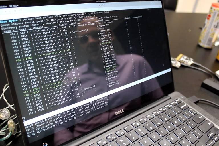 Reflexo do hacker é visto à frente de tela escura do computador, com informações de bluetooth na região