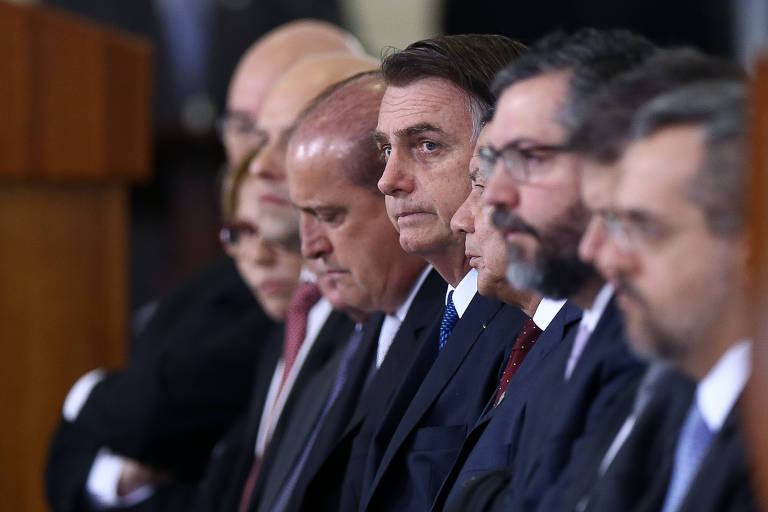 Ao lado de ministros, o presidente Jair Bolsonaro (PSL) acompanha cerimônia no Palácio do Planalto, em Brasília