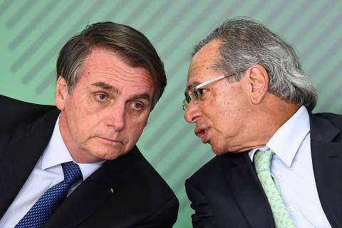Brazilian President Jair Bolsonaro (L) listens to his Economy Minister Paulo Guedes during a ceremony to sanction of a law that will offer lower bank rates for people who do not have debts, at Planalto Palace in Brasilia, on January 12,  2019. - Brazilian President Jair Bolsonaro on Monday sacked his education minister, an ultraconservative who had drawn public ire over a range of controversial proposals including a revision of school textbooks to deny the 1964 military coup. (Photo by EVARISTO SA / AFP) ORG XMIT: ESA267