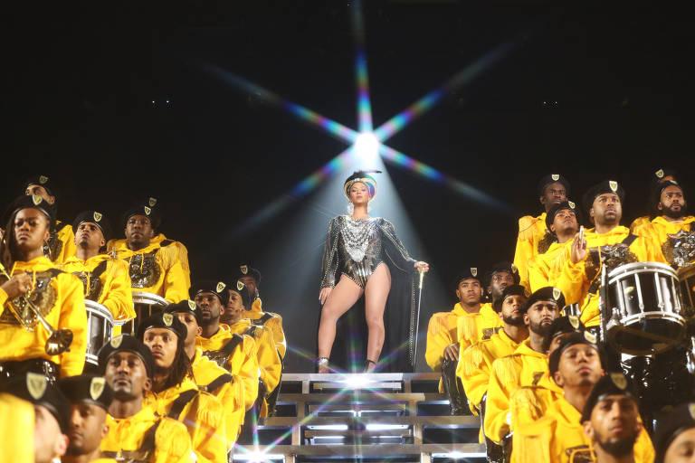 Beyoncé no palco, em cima de estrutura de escadas, cercada por dançarinos e músicos de amarelo