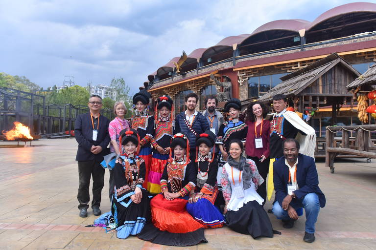 A escritora Francesca Cricelli (em pé, de vermelho) com dançarinos em de Sichuan, na China