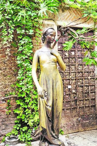 Estátua de Julieta, cujos seios são apalpados por turistas
