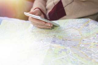 hand with mobile phone pointing to the map, travel and vacation