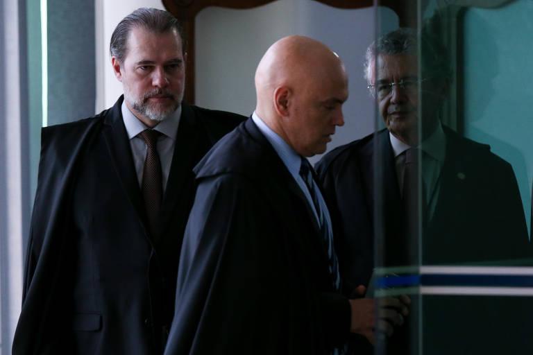 Os ministros do STF Dias Toffoli, Marco Aurélio Mello e Alexandre de Moraes passando por uma porta de vidro