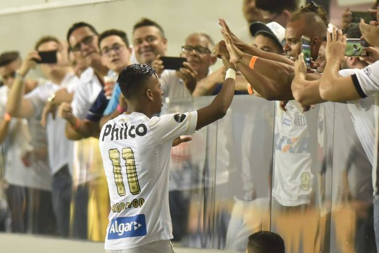 Após marcar o primeiro gol do Santos na Vila Belmiro, o atacante Rodrygo cumprimenta alguns torcedores santistas que se aglomeraram rente à grade de acrílico que separa a arquibancada do campo